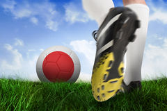 Football boot kicking japan ball. Composite image of football boot kicking japan ball against field of grass under blue sky Stock Images