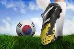 Football boot kicking korea republic ball. Composite image of football boot kicking korea republic ball against field of grass under blue sky Stock Images