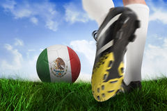 Football boot kicking mexico ball. Composite image of football boot kicking mexico ball against field of grass under blue sky Royalty Free Stock Photo