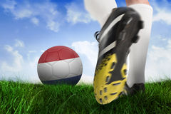 Football boot kicking netherlands ball. Composite image of football boot kicking netherlands ball against field of grass under blue sky Royalty Free Stock Photo