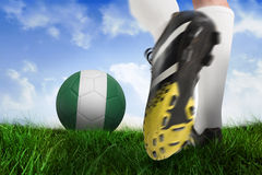 Football boot kicking nigeria ball. Composite image of football boot kicking nigeria ball against field of grass under blue sky Royalty Free Stock Images