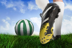 Football boot kicking nigeria ball. Composite image of football boot kicking nigeria ball against field of grass under blue sky Royalty Free Stock Photography