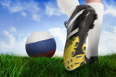 Football boot kicking russia ball. Composite image of football boot kicking russia ball against field of grass under blue sky Stock Photo