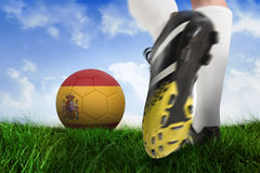 Football boot kicking spain ball. Composite image of football boot kicking spain ball against field of grass under blue sky Royalty Free Stock Image