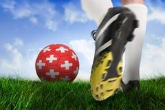 Football boot kicking switzerland ball. Composite image of football boot kicking switzerland ball against field of grass under blue sky Stock Photo