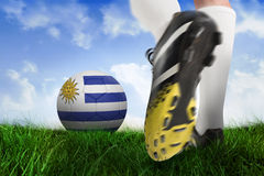 Football boot kicking uruguay ball. Composite image of football boot kicking uruguay ball against field of grass under blue sky Royalty Free Stock Photo