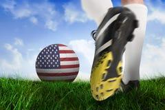 Football boot kicking usa ball. Composite image of football boot kicking usa ball against field of grass under blue sky Stock Photography