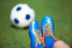 Football boots of boy soccer player with ball on green Royalty Free Stock Photography
