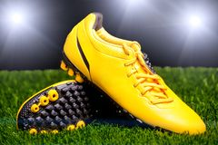 Football boots on the grass. In the stadium floodlights Stock Photography