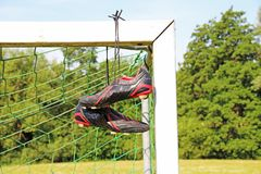 Football boots hanging on a football post Stock Image