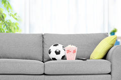 Football and a box of popcorn on a modern sofa Royalty Free Stock Images