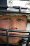 Youth football. Close up of a young, sweating, boy wearing a football helmet and a serious look Stock Images