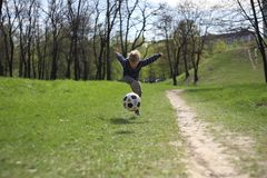 Football boy ball kick game park jump game. Little boy hits the football ball heavily in the jump from the dispersal stock photography