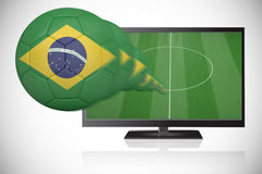 Football in brasil colours flying out of tv Stock Photography