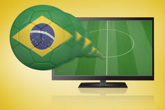 Football in brasil colours flying out of tv Stock Photos