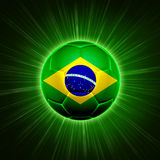 Football with Brazilian flag over green rays. Football - 3d shining soccer ball with Brazilian flag with lights and rays over green background Royalty Free Stock Photography