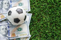 Football Business Concept : A fooball on dollar bills and green royalty free stock photo