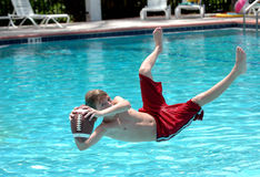 Football catch. A boy catches the football while jumping in the pool Royalty Free Stock Photography