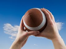 Football Catch. Two hands catching a football with cloudy sky background Stock Images