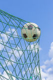 Football caught in goal net with blue sky Royalty Free Stock Photos
