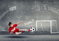 Football champion. School aged boy on sketched background playing football Royalty Free Stock Image