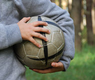 Football in the child hands, close-up Stock Photos