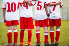 Football children team. Kids soccer substitute players standing together on a row. Football sports tournament for young boys. Four kids watching football stock photos