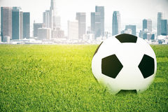 Football on city background. Closeup of football on grass. City background. 3D Rendering Royalty Free Stock Image