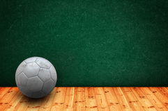 Football class. Soccer ball on the classroom floor in front of the green chalkboard royalty free stock photography