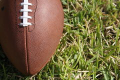 Football close up. A close up of a brown football ball lying in the grass of the lawn on the field outdoors Royalty Free Stock Images