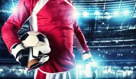 Goalkeeper holds the ball in the stadium during a football game. Football close up scene of a goalkeeper at the stadium royalty free stock photography