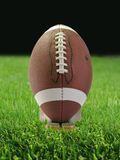 Football. Closeup of a football on a grass field at night Stock Image