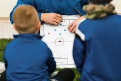 Football Coach Coaching Kids. Young Soccer Players Listening Coaches Tactics and Motivational Talk. Speech stock photography
