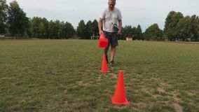 Football coach collects the cones from the field. In summer day stock footage