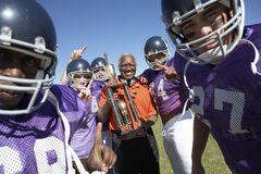 Football Coach and Players holding trophy on field Royalty Free Stock Photos