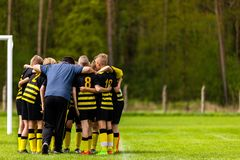 Football Coaching. Young Boys Having Pep Talk with Coach Before the Tournament Match. Kids Soccer Academy Team on the Pitch. Youth Soccer Coach Coaching Stock Images