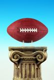 Football On Column Pedestal. Symbol of sports. Vertical photo. Gradient blue background. Stone like pedestal. Symbolic of winners and successful season stock photo