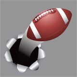 Football coming out of hole Stock Photo