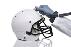 Football Concussion Concept. A football helmet and doctors hand holding a stethoscope on the crown of the helmet. Sports Concussion Concept, and related Royalty Free Stock Photography