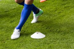 Football Cone and Player. A football cones placed on the pitch ready to be used by the players for football training stock photo