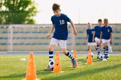 Football Drills: The Slalom Drill. Youth soccer practice drills. Young football players training on pitch. Soccer slalom cone drill. Boy in blue soccer jersey stock photos