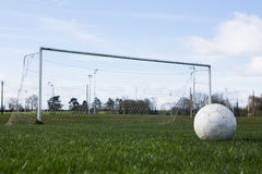 Football on an empty pitch in front of goal Royalty Free Stock Image