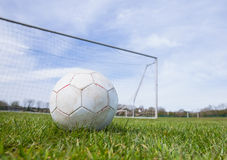 Football on an empty pitch in front of goal Royalty Free Stock Photos