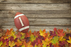 Football with fall leaves on rough wood top view Royalty Free Stock Image