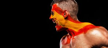 Soccer or football fan with bodyart on face with agression - flag of Spain. Royalty Free Stock Photos