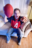 Football: Fan On Couch Cheers For Team Stock Images