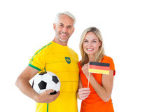 Football fan couple cheering and smiling at camera Royalty Free Stock Photo