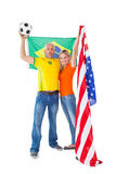 Football fan couple cheering and smiling at camera Stock Images