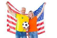 Football fan couple cheering and smiling at camera Stock Photos