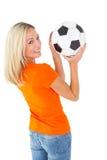 Football fan holding ball in orange tshirt Royalty Free Stock Photo